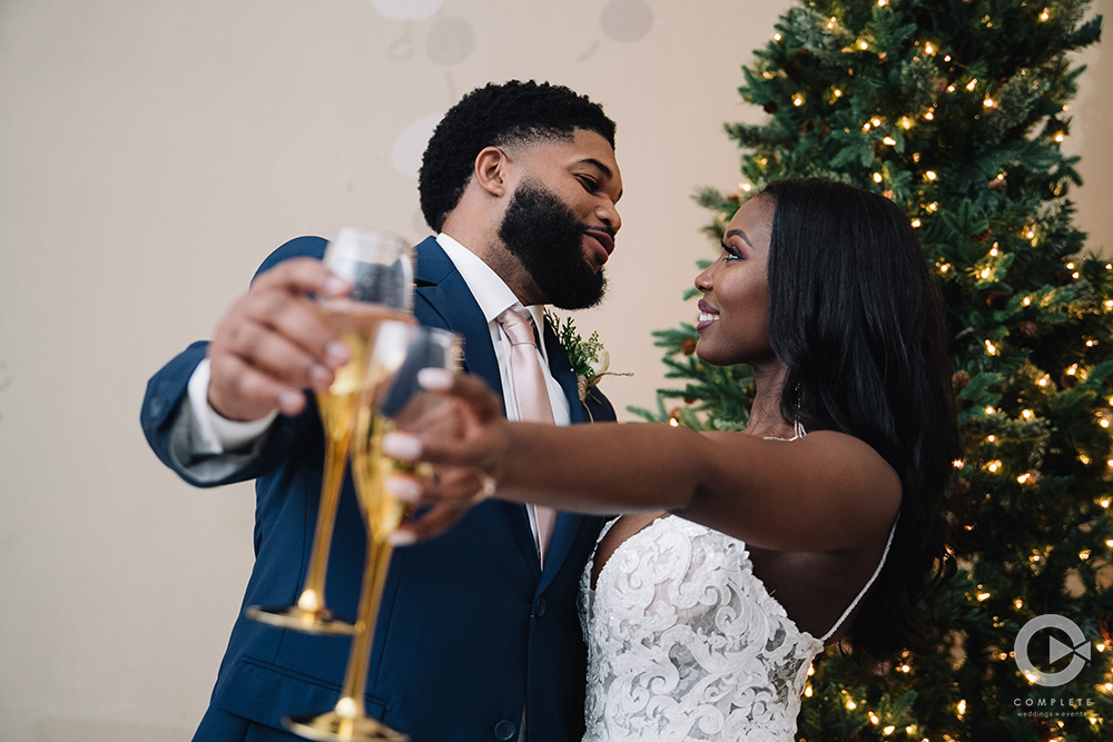 bride and groom toast in front of christmas tree