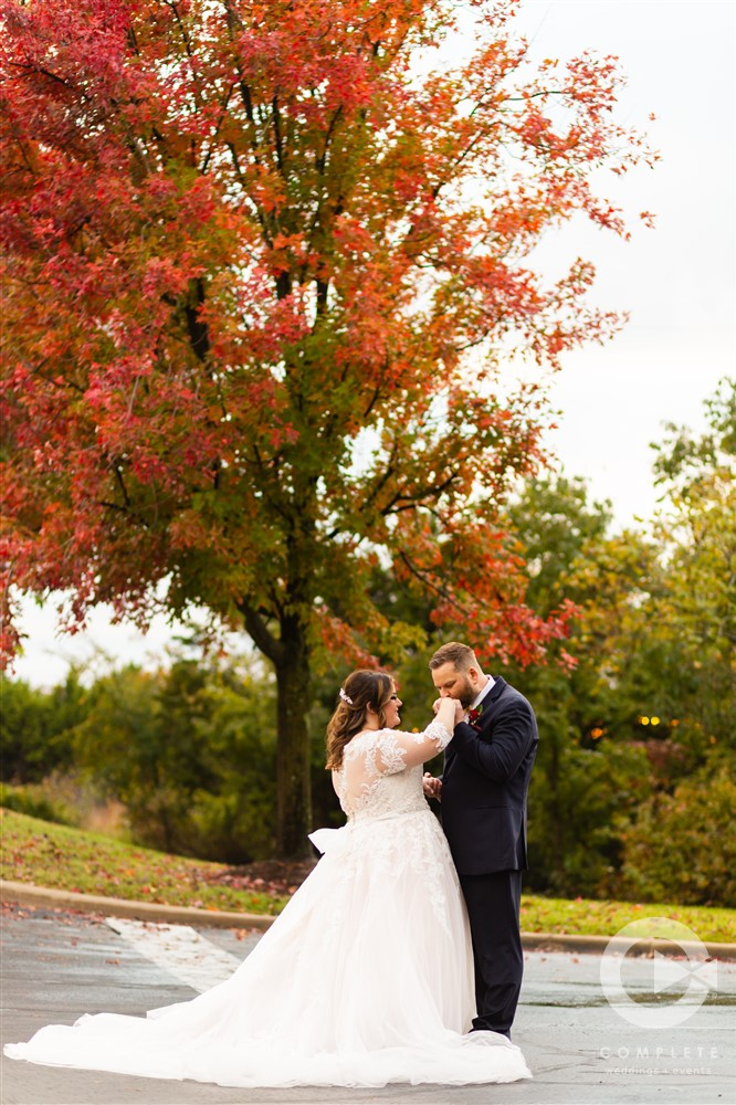Groom kissing brides hand under red tree