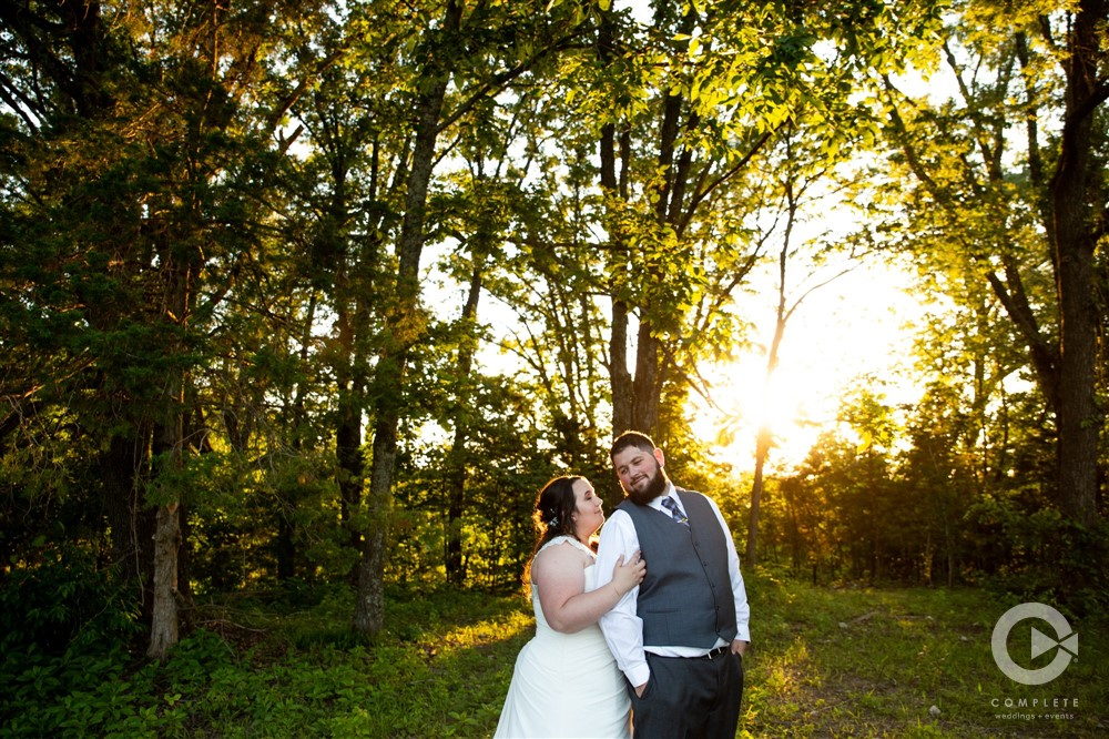 bride and groom in the forest at sunset