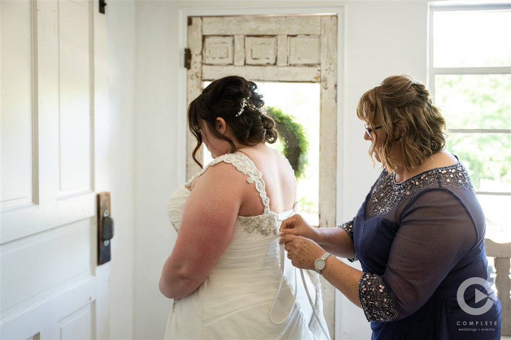 bride having her dress laced in preparation for ceremony