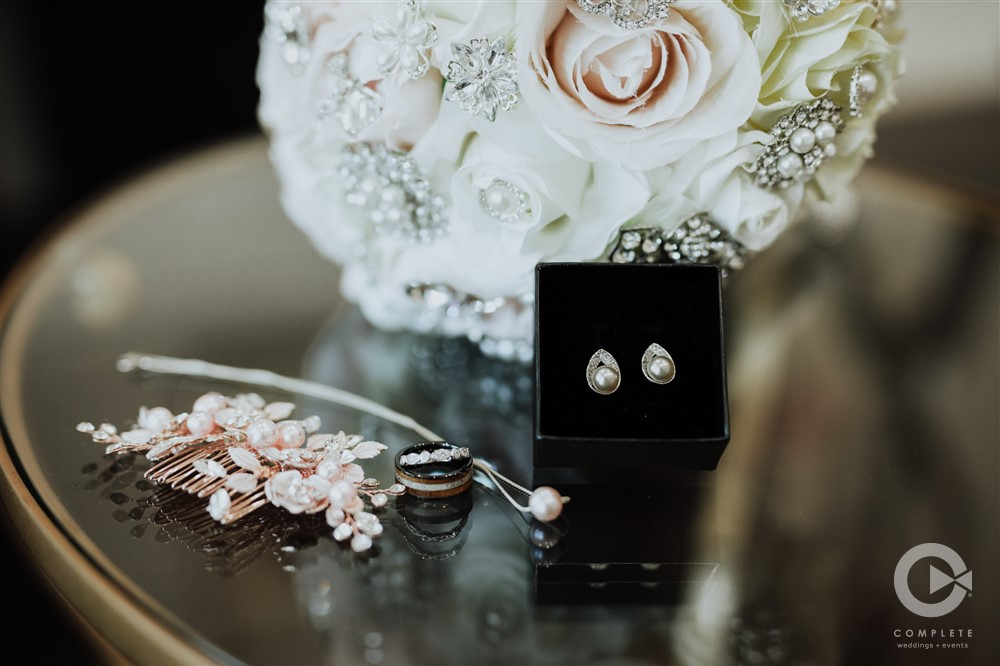 focus shot of wedding ring, earrings, and bridal bouquet
