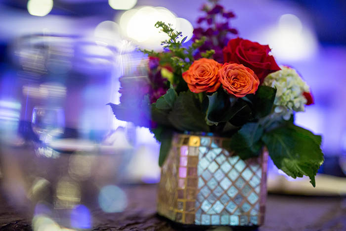 Purple up-lighting with red and orange floral center pieces
