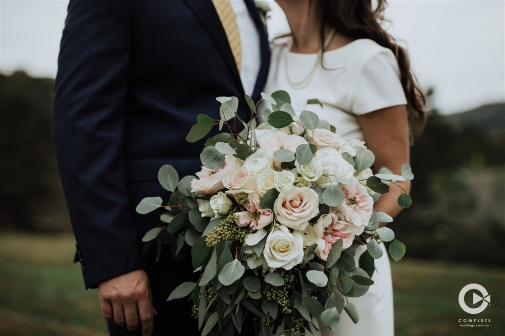 White and cream roses with accents of greenery and pink peonies created by Artistry in Bloom
